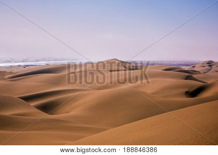 Atlantic in Namibia, Africa. Giant sand dunes on the ocean coast. The concept of exotic and extreme travel