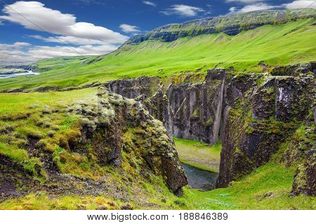 Green Tundra in July. The concept of active northern tourism. The striking canyon in Iceland. Bizarre shape of cliffs surround the stream with glacial water