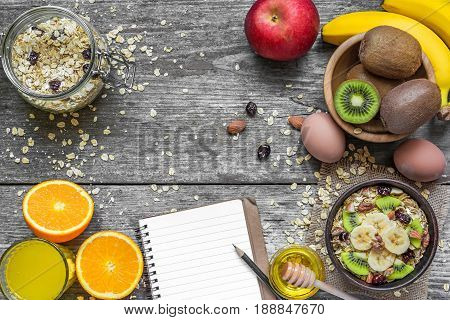 healthy breakfast with oats fruits berries egg honey and orange juice with blank notebook on rustic wooden background with copy space. top view