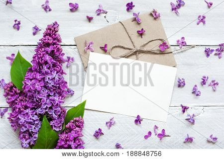 blank white greeting card with lilac flowers bouquet and envelope on white wooden background. top view. mock up