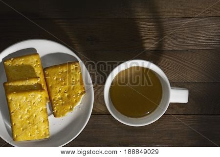 Biscuits sprinkle sesame and hot coffee on wood background.