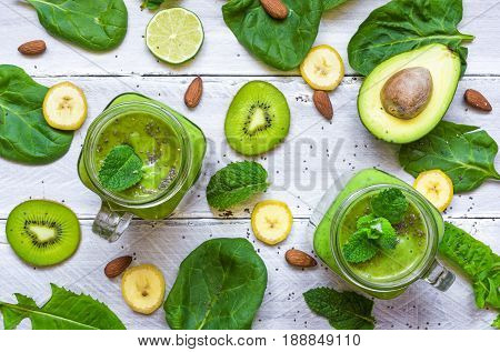 healthy green smoothie with avocado banana spinach mint almonds and chia seeds in glass jars on white wooden background. top view