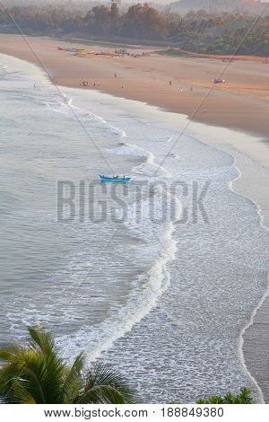 Morning landscape. Sandy sea beach and fishermen in a boat. Gokarna India