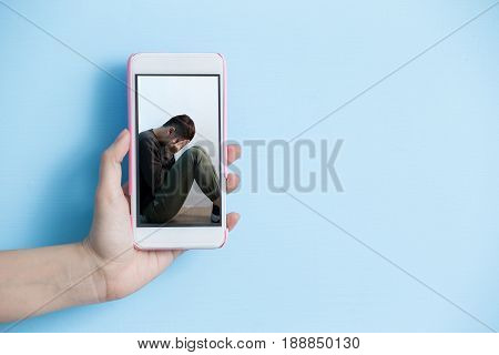 hand take smart phone with internet bullying concept in screen on blue background