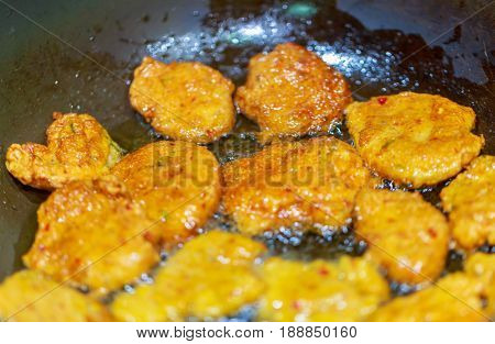Deep fried fish cake in the pan on stove a famous Thai traditional food.