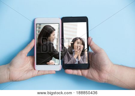 hand take smart phone with internet bullying concept on blue background