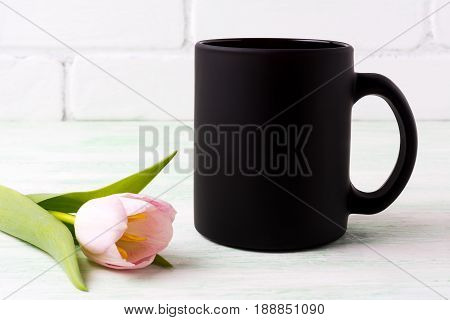 Black coffee mug mockup with tender pink tulip flower. Empty mug mock up for brand promotion.