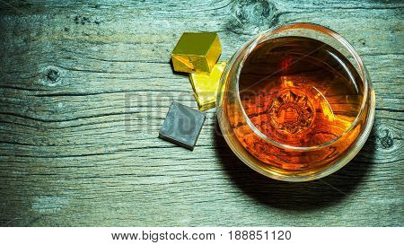 Whiskey glass and chocolate on wooden background top view.