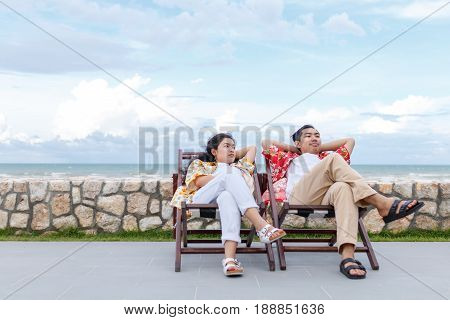 couple asian man and woman with yellow and red shirt sitting beautiful sky background