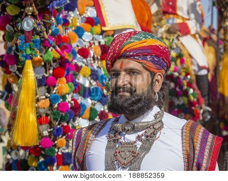 JAISALMER INDIA - FEBRUARY 08 2017 : Camel and indian men wearing traditional Rajasthani dress participate in Mr. Desert contest as part of Desert Festival in Jaisalmer Rajasthan India