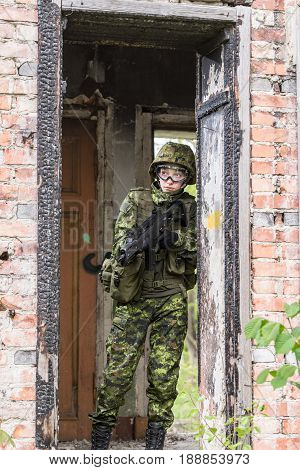Portrait of armed woman with camouflage. Young female soldier observe with firearm. Child soldier with gun in war hearth house ruins background. Military army people concept
