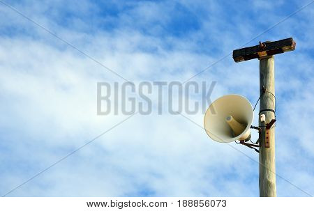 Outdoor loudspeaker warning system on telegraph pole against a blue sky background. Copy space for text.