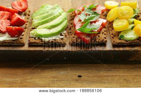 Sandwiches rye crisp with avocado, tomato and strawberry