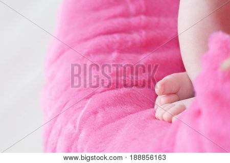 Newborn feet closeup baby girl heels on pink background of mohair blanket soft and cute