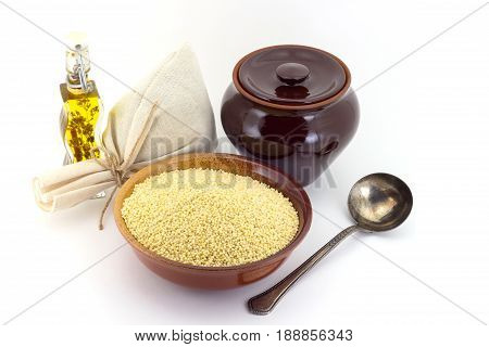 Still life of Millet cereal in ceramic pial, ceramic pot, old spoon and canvas bag for cereals, oil with spices and seasonings, isolated on white background