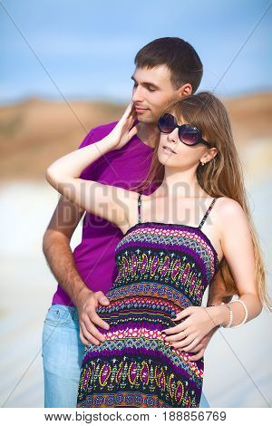 tender couple on romantic travel honeymoon vacation summer holidays romance. Young happy couple on the beach with white sand, caucasian woman and man embracing outdoors