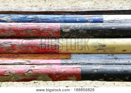 Multicolored image of show jumping poles stacked at the show jumping arena
