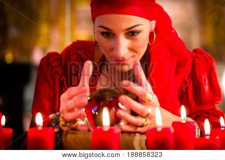 Female Fortuneteller or esoteric Oracle, sees in the future by looking into their crystal ball during a Seance to interpret them and to answer questions poster
