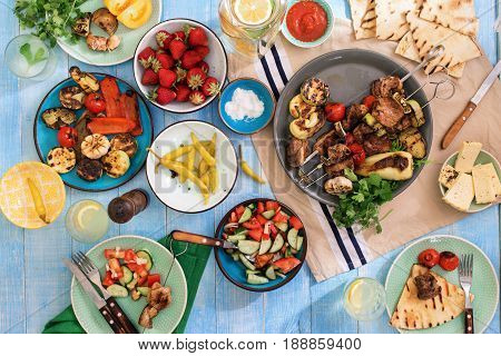 Shish kebab various grilled vegetables salad lemonade strawberries and snacks on a blue wooden table top view. Dinner table concept