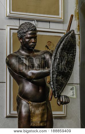Moscow, Russia - March 19, 2017: Antique statue of an African aborigine warrior or hunter with a spear and shield, in a traditional loincloth, art object and a collectible, for sale on the flea market