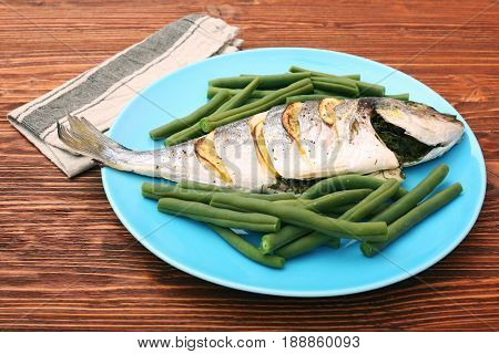 Grilled sea bream fish with green beans on wooden background