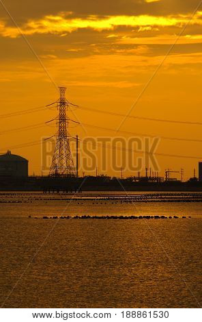 Coastal industrial estates and the hight voltage power line in the evening sunlight