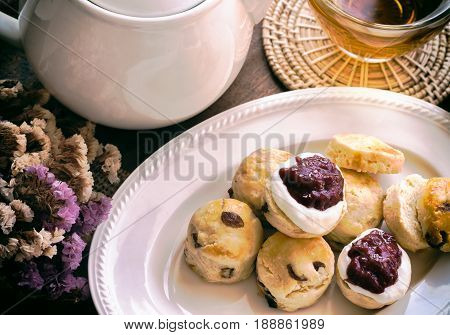 Homemade raisin scones serve with homemade strawberries jam,clotted cream and tea. Scones is English pastry for afternoon tea,cream tea. Delicious scones Devon shire or Cornish cream style. Homemade scones Cornish style in afternoon tea.
