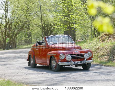 STOCKHOLM SWEDEN - MAY 22 2017: Red Volvo PV Cabriolet classic car from 1961 driving on a country road in the public race Gardesloppet in the forests at Djurgarden Stockholm Sweden. May 22 2017
