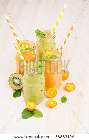 Freshly blended orange kumquat and green kiwi fruit smoothie in glass jars with straw mint leaf cut ripe berry. White wooden board background vertical.
