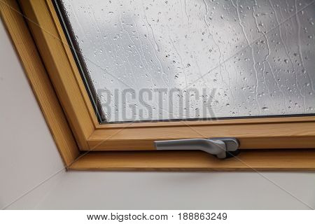 New roof window during the rains with drops on the glass.