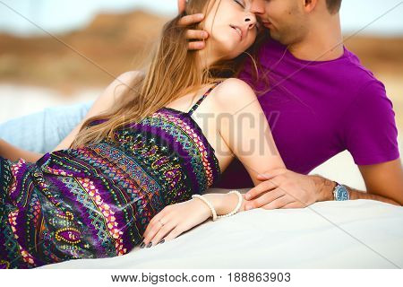 Lovers lie on the beach. romantic travel honeymoon vacation summer holidays. young girl dressed in a colorful dress and man in a violet t-shirt. they embracing outdoors