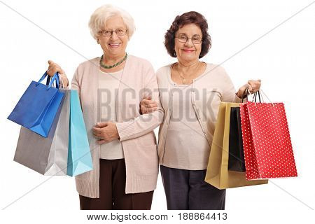 Two mature women with shopping bags looking at the camera and smiling isolated on white background
