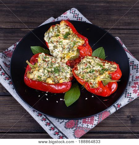 Red peppers stuffed with cream cheese with herbs and garlic baked in grill in black plate close up
