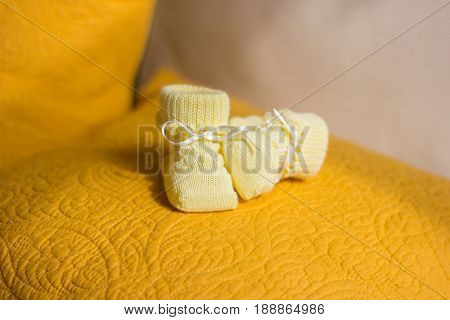 Children's yellow bootees on a yellow pillow