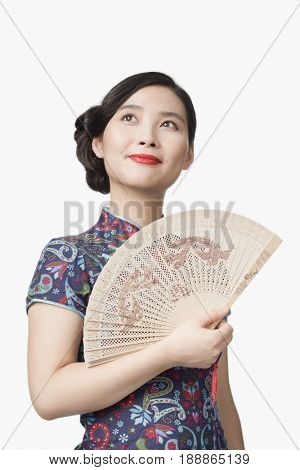 Smiling Chinese woman in traditional clothing holding fan