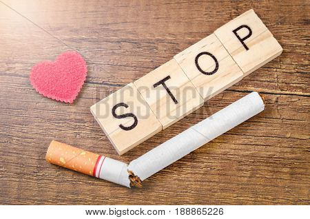 STOP word and tobacco with red heart on wooden background. World No Tobacco Day