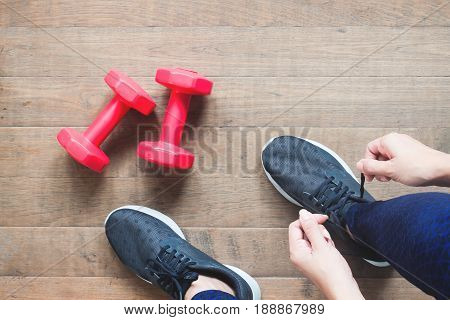 Tying sport shoes Asian woman getting ready for weight trainning. Exercise Fitness training. Healthy lifestyle concept