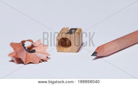 A wooden simple pencil a pencil sharpener and shavings lie on a white isolated background.