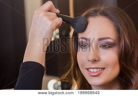 Make-up artist puts powder on the face of a beautiful brunette girl in the beauty salon. Professional cosmetics make-up and skin care.