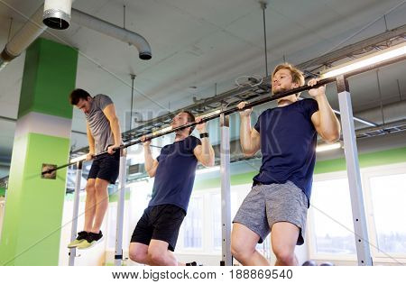 sport, fitness and people concept - group of young men exercising and doing pull-ups on horizontal bar in gym