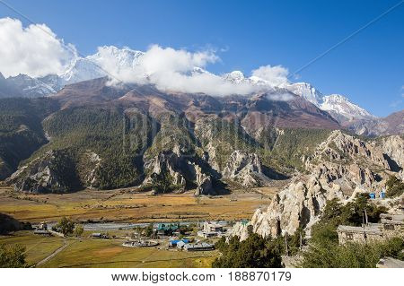Traditional stone build village of Manang. Mountains in the background. Annapurna region Nepal. Sunny day of Nepal summer. Big mountain stone houses blue river and fresh air. Eco travel