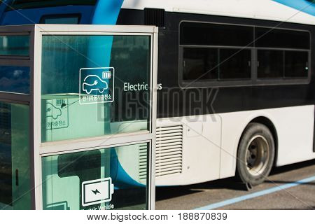 Electric vehicle bus stands at the charger.