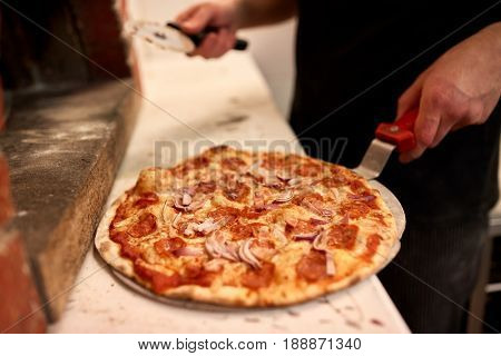 food, italian cuisine, people and cooking concept - cook with pizza peel and cutter at pizzeria