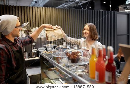 small business, takeaway food, people and service concept - happy female customer taking paper bag from man or barman at vegan cafe