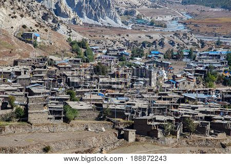 Traditional stone build village of Manang. Mountains in the background. Annapurna region Nepal. Sunny day of Nepal summer. Mountain stone houses blue river and fresh air. Eco travel