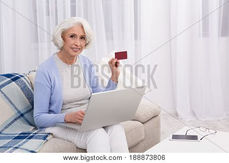 Elderly woman using credit card number for buying goods in online market. Beautiful woman using laptop computer and showing credit card to camera.