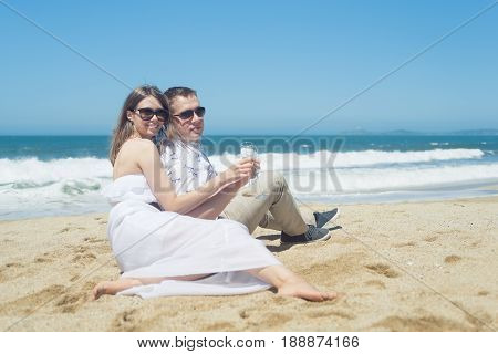 Young romantic couple sitting on the beach, man in sunglasses, woman in white dress, holding glasses, drinking champaign.