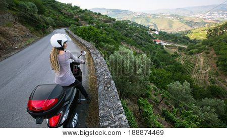 Young woman with blond dreadlocks travels on a motorcycle on the Douro Valley, Portugal. Looking from the top to Vineyards on a hills.