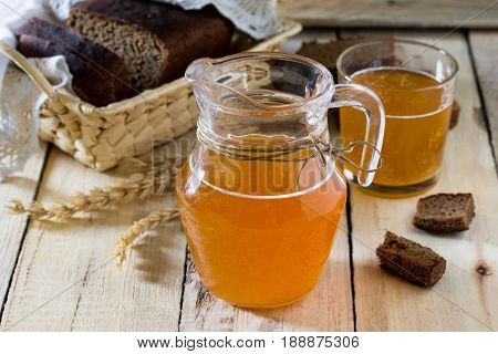 Traditional Russian Cold Rye Drink Kvas In A Glass And A Jug On The Kitchen Table In A Rustic Style.