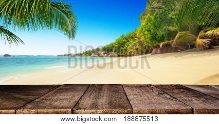 Tropical beach with empty wooden table, summer holiday background. Travel and beach vacation, free space for text or product placement.